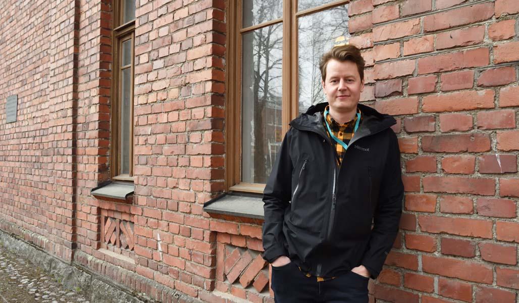 Jaakko Puputti nojaa punatiiliseinään Hämeenlinnan kasarmialueella.