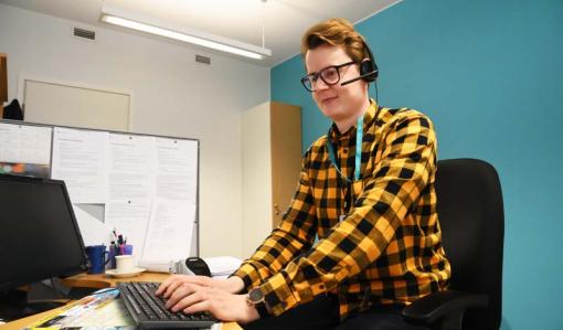 Asiakasneuvoja Jaakko Puputti istuu työpisteellään. Hänellä on luurit päässä ja hän näppäilee tietokoneen näppäimistöä. Huoneessa on turkoosinsininen seinä.