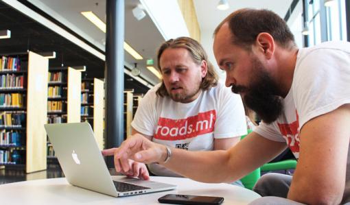 Antti Mattila ja Jussi-Pekka Martikainen katsovat kannettavaa tietokonetta valoisassa kirjastossa.