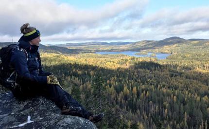 Eräopas Saana Lappalainen istuu rinkka selässä Kolilla korkealla kalliolla. Oikealle avautuu metsäinen maisema.