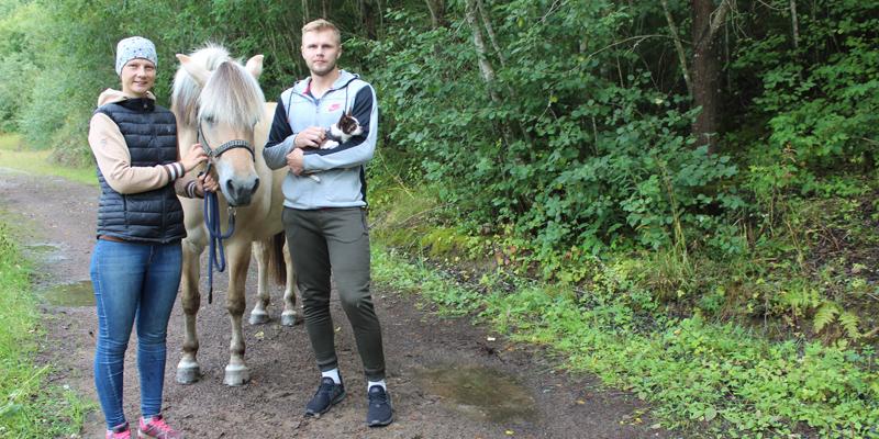 Salla ja Samu Jokela seisovat hevosen kanssa metsäpolulla. Ympärillä on rehevää kesäistä metsää.