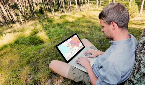 Mies istuu nurmikolla kannettava tietokone sylissään ja katsoo oman metsänsä tietoja Metsään.fi-palvelusta. Hän nojaa puuhun. Miehen ympärillä on nurmikkoa ja taustalla on metsää.