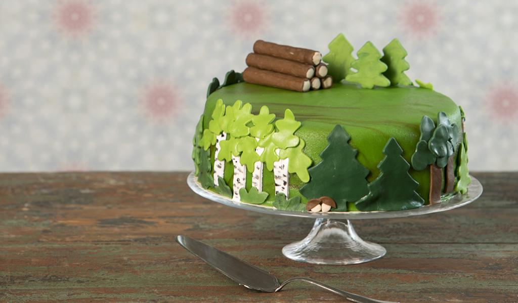 Juhlakakussa on vihreä marsipaanikuorrutus. Kakku on koristeltu marsipaanista tehdyillä kuusi- , mänty- ja koivukuvioilla. Marsipaanista on tehty kakun päälle koristeeksi myös tukkipino.