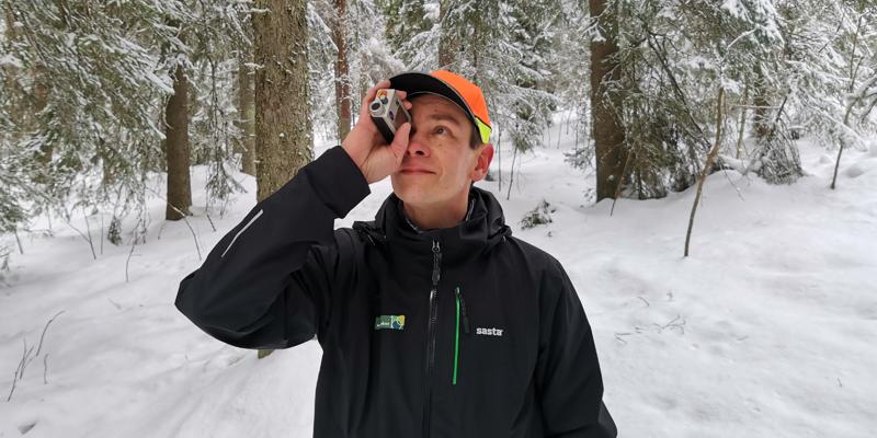 Metsäneuvoja Ari Kasanen katsoo ja mittailee korkeusmittarilla puustoa talvisessa metsässä.