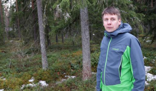 Rami Mattila seisoo omassa metsässään. Taustalla on kuusia ja varvikkoa sekä maassa on hieman lunta.