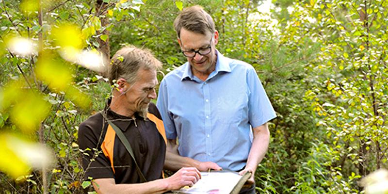 Tapio Muotio ja Esko Lehtimäki katsovat yhdessä karttaa Lehtimäen metsätilasta.