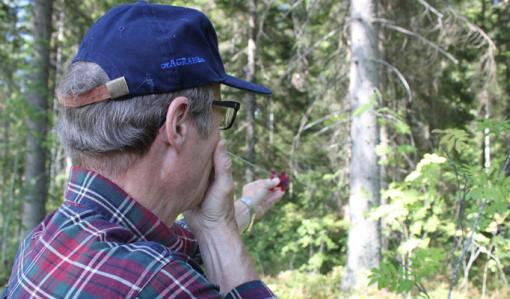 Metsän- ja luonnonhoidon asiakasneuvoja Kari Vääränen mittaa metsää ketjurelaskoopin avulla. Relaskoopin ketjun pää on silmän kohdalla ja Vääränen tähtää relaskoopilla kohti puiden runkoja.