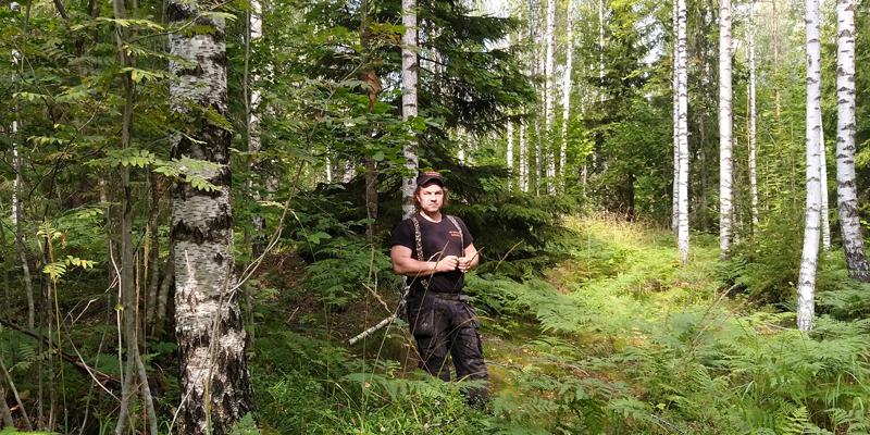 Tuomas Korpijaakko seisoo keskellä kuvaa omassa metsässään, jossa kasvaa sekapuustoa. Kuvassa hänen ympärillään on koivuja, pihlajia, kuusia ja saniaisia.