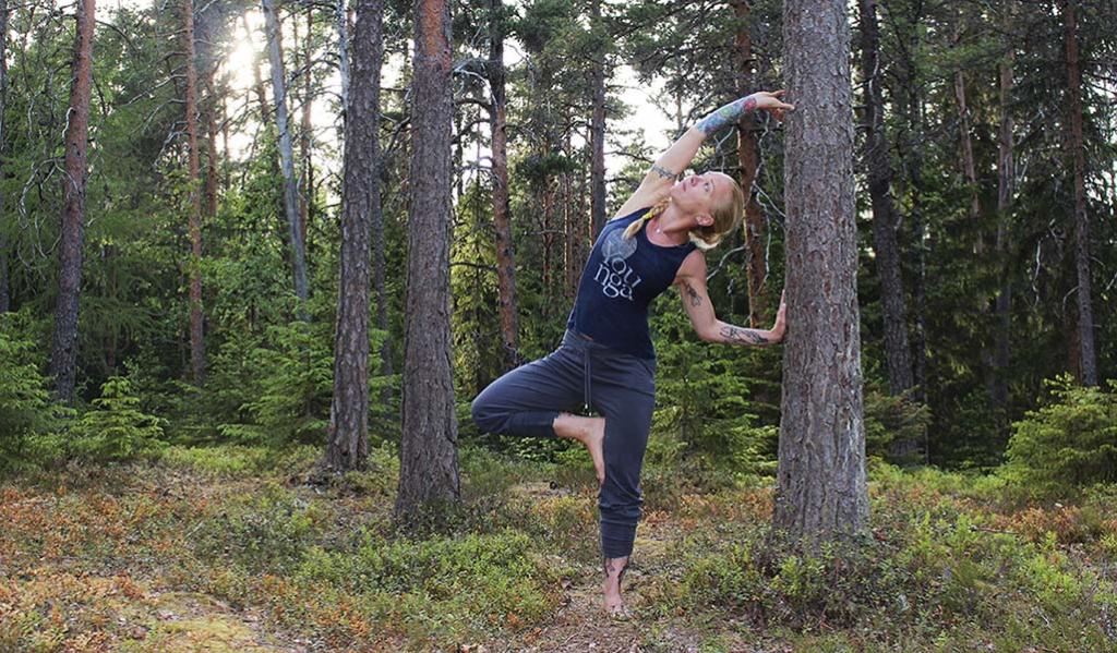 Eva Travanti ohjaa metsäjoogaa. Hän venyttää toista kylkeä männyn runkoa kohti. Ympärillä on metsää.