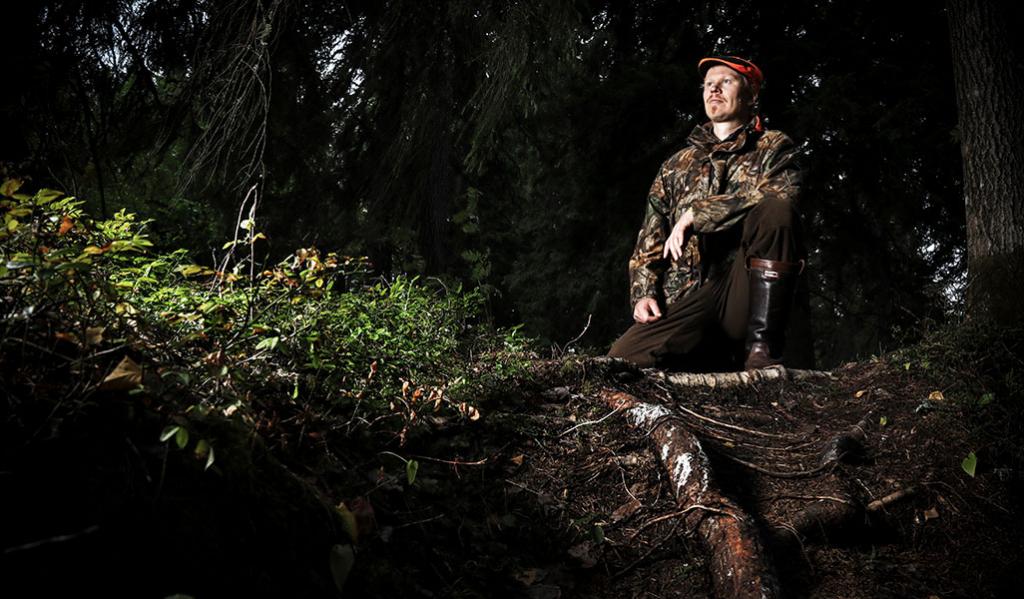Riistasuunnittelija Teemu Lamberg on nostanut jalkansa ison puun juurakon päälle. Ympärillä on tummasävyistä metsää ja maassa varvikkoa.
