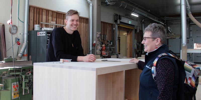 Miikka Kotilainen juttelee puisen pöytätason takaa yritysneuvoja Leila Laukkaselle Puuartistin tuotantotiloissa.