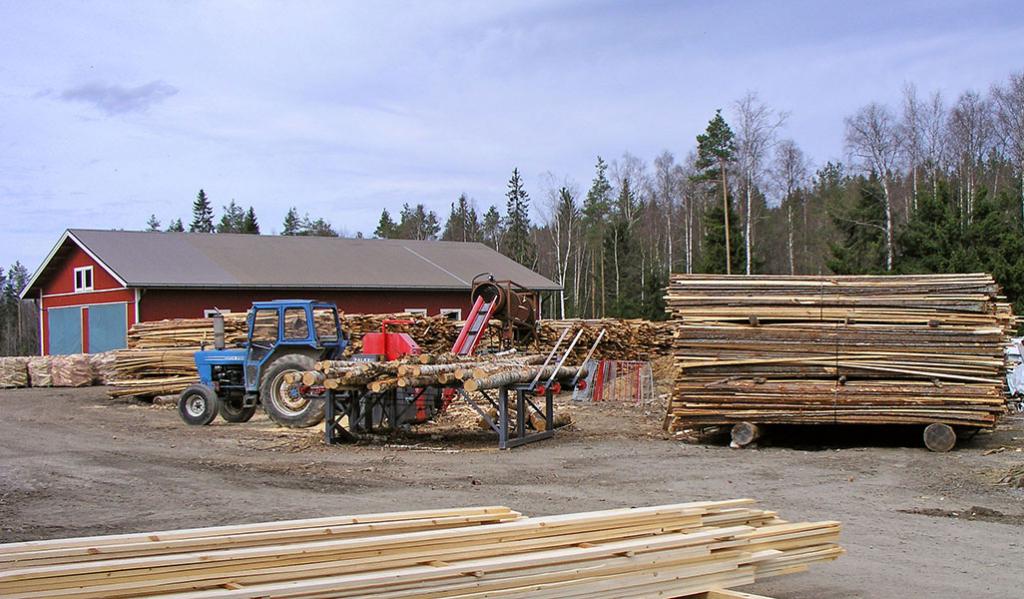 Kolkonjoen sahan piha-alueella kulkee traktori ja pinoissa on sahatavaraa.