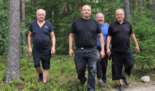 Reijo, Toni, Jani ja Mika Peräkangas kävelevät rinnakkain metsässä.