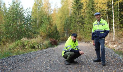 Tieisännöitsijä Tomi Vähä-Kouvola on kyykyssä metsätiellä ja hänen vieressään seisoo Tapio Kahilaniemi. Tielle on pudonnut keltaisia lehtiä ja tien ympärillä on metsää.