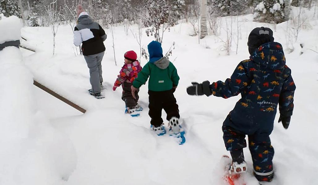 Aikuinen ja kolme lasta kulkevat hangessa lumikengillä talvella.