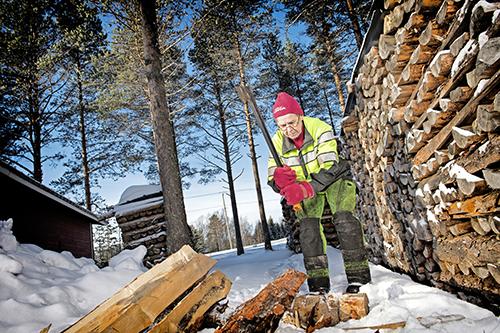 Marjatta Kyllönen halkoo kirveellä puita klapeiksi. Vieressä oikealla on yli metrin korkea halkopino. Maassa on lunta ja taustalla on pihapiirin mäntyjä.