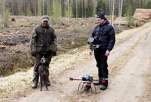 Tommi Kinnunen ja saksanseisoja Heta ja VideoDrone Oy:n Juhani Mikkola seisovat metsätiellä hakkuuaukon reunalla. Mikkolan kaulassa on lämpökamera ja maassa tiellä on drone.