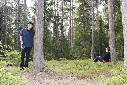 Mari Jussila ja Minna Sundman nojaavat kilpikaarnaisiin mäntyihin. Ympärillä on metsää.