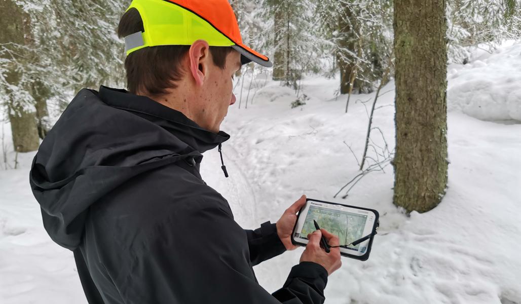 Ari Kasanen katsoo tietoja maastotallentimelta talvisessa metsässä.