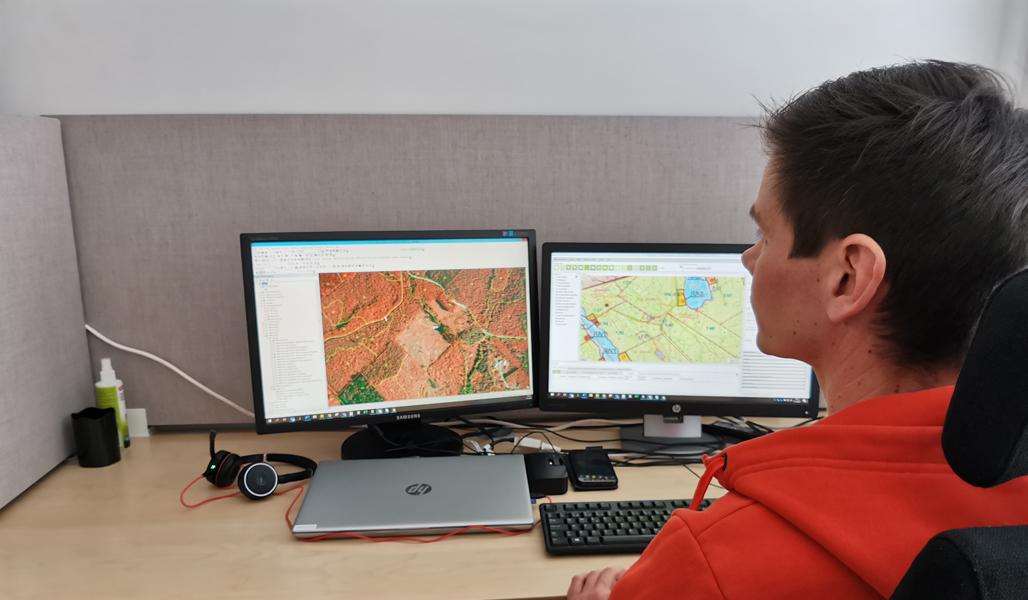 Ari Kasanen katsoo karttakuvia kahdelta tietokonenäytöltä työpisteellään.