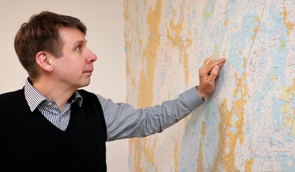 Rami Mattila katsoo seinällä olevaa maastokarttaa. Hän osoittaa kartalta sormellaan pistettä, missä hänen metsiään on.