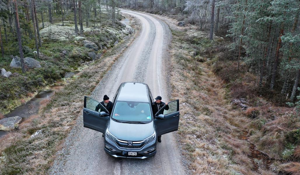 Kuvassa on auto kuvattuna ylhäältäpäin metsätiellä. Miehet nousevat autosta.