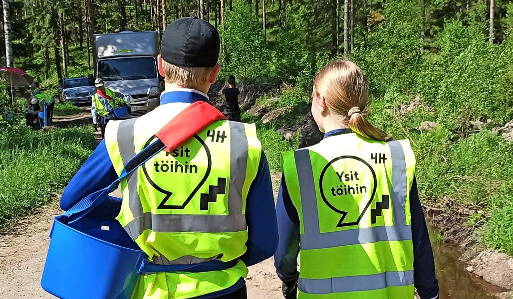 """Kaksi nuorta seisovat metsätiellä selkä kameraan päin """"Ysit töihin""""-huomioliiveissä.."""