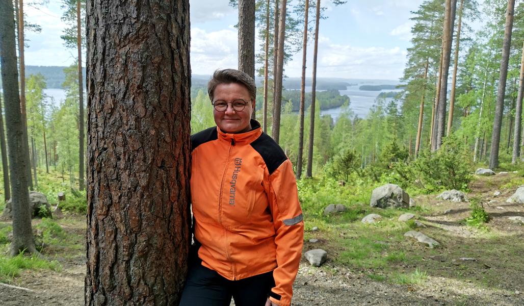 Anne Ruokonen männyn vieressä. Taustalla metsää ja järvimaisemaa.