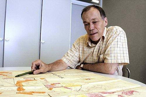 Metsätietopäällikkö Raito Paananen katselee vanhaa käsin piirrettyä metsäkuviokarttaa, joka on levitetty hänen työhuoneensa pöydälle.