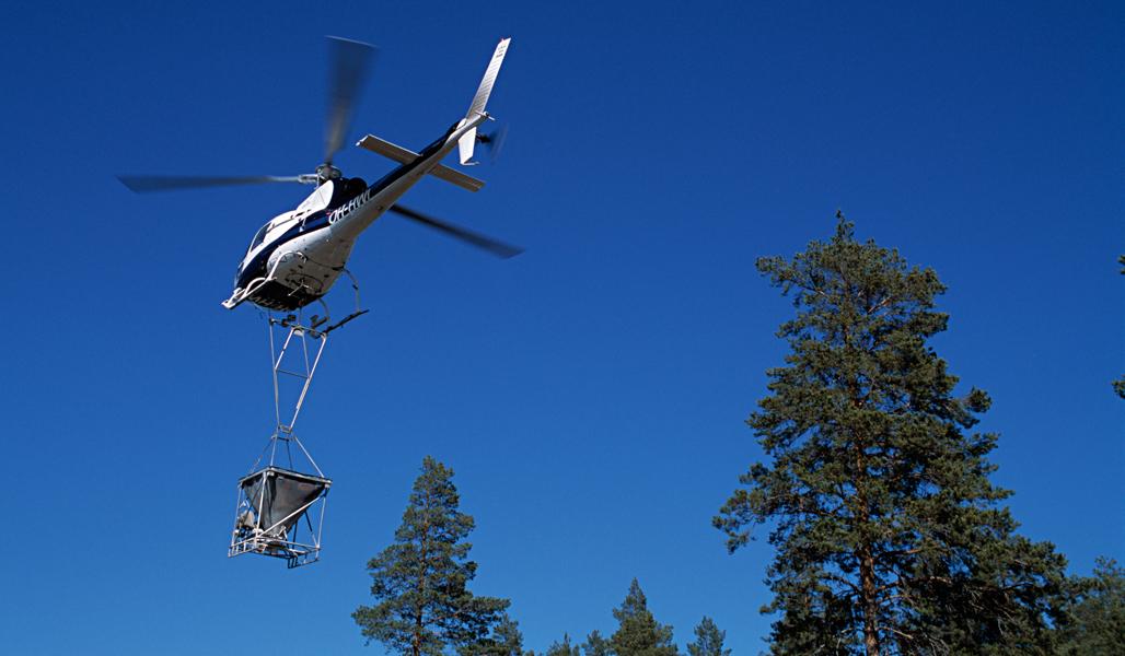 Helikopteri lentää kirkkaansinisellä taivaalla. Helikopterin alla olevasta astiasta pudotetaan tuhkaa metsään. Kuvan oikeassa alareunassa näkyy hieman männynlatvaa.