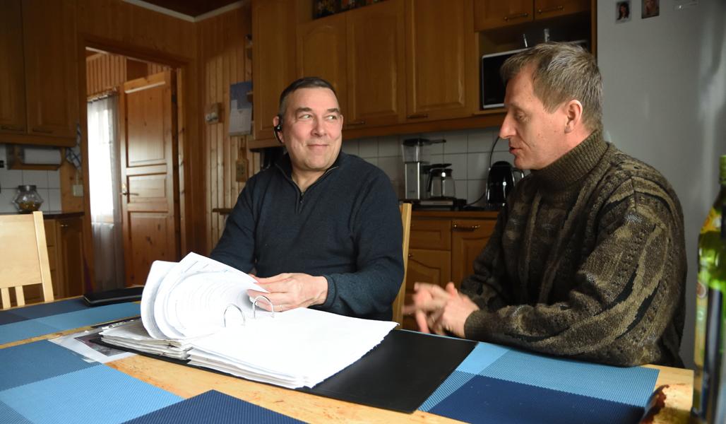 Ari Sirviö ja Markku Remes istuvat keittiössä pöydän ääressä. Sirviö selaa vanhoja tuhkalannoitussuunnitelmia.