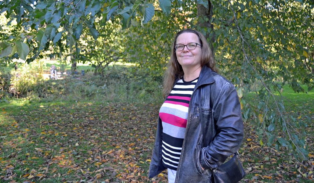 Raisa Mäkipää kuvattuna lehtipuun alla syksyisessä puistossa.
