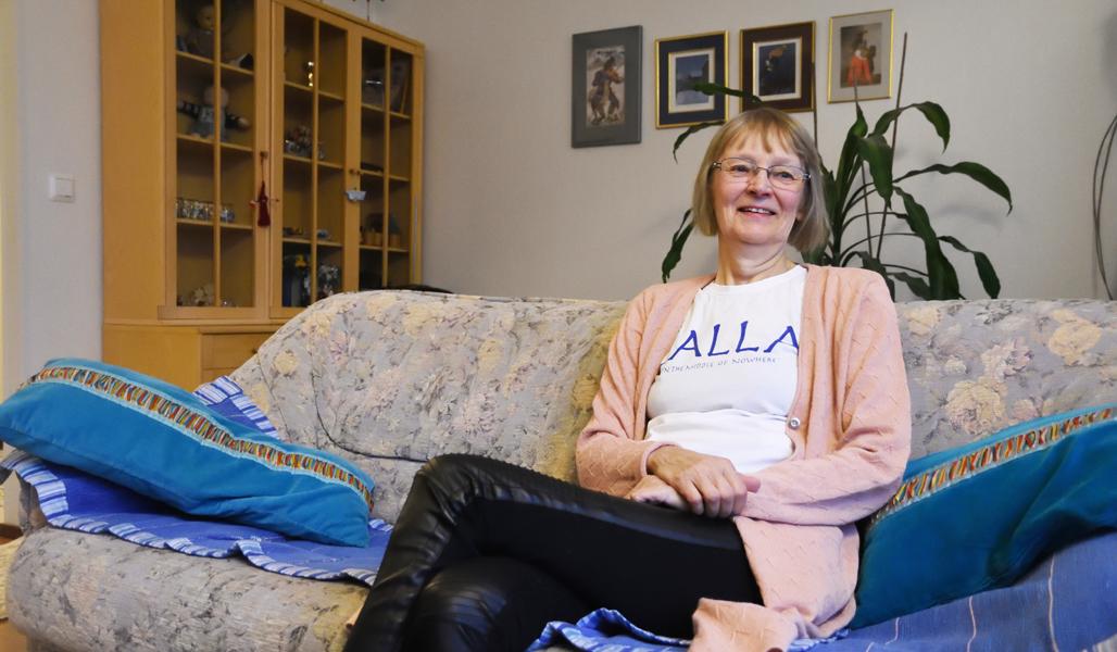Ansa Lassila istuu kotonaan kukikkaalla sohvalla. Taustalla on tauluja ja viherkasvi sekä vitriinikaappi.